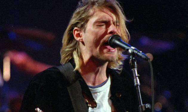 FILE - This Dec. 13, 1993 file photo shows Kurt Cobain of the Seattle band Nirvana performing in Seattle, Wash. It's been two decades since the Nirvana frontman took his own life yet he remains on in the thoughts of those he influenced and entertained. He's a touchstone for young musicians clutching guitars the world over and his story is a tale of both inspiration and caution. His influence still ripples across the surface of pop music and his shadow even looms in the hip-hop world where he's been a referenced by Jay Z, Kanye, Kendrick Lamar, Drake and Jay Electronica in various ways recently. (AP Photo/Robert Sorbo, file)