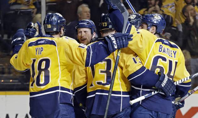 Nashville Predators center Nick Spaling (13) celebrates with Brandon Yip (18), Rich Clune, second from left, and Victor Bartley (64) after Spaling scored against the Calgary Flames in the second period of an NHL hockey game, Thursday, March 21, 2013, in Nashville, Tenn. (AP Photo/Mark Humphrey)