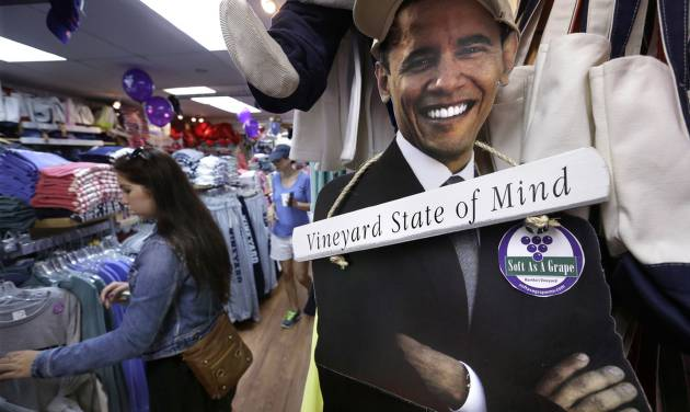 FILE - In this Aug. 9, 2013 file photo Meghan Ford of Marshfield, Mass., left, looks through a rack of clothes near a cut-out photograph of President Barack Obama, right, at a shop in Oak Bluffs, Mass., on the island of Martha's Vineyard.  President Obama and his family are returning to the island off the Massachusetts mainland Saturday, Aug. 9, 2014, for the longest summer vacation of his six-year presidency. (AP Photo/Steven Senne, File)