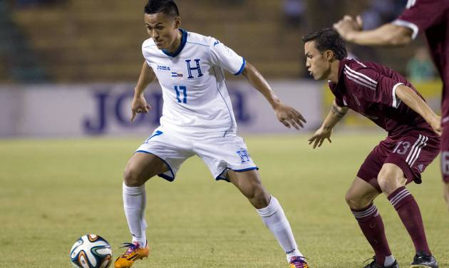 FILE - In this March 5, 2014, file photo, Honduras' Andy Najar, left, moves the ball away from Venezuela's Luis Manuel Seijas during their international friendly soccer match at Estadio Olimpico in San Pedro Sula, Honduras. Najar, who chose to play for Honduras rather than wait for U.S. citizenship, was among 23 players selected for the Catrachos' World Cup roster. (AP Photo/Moises Castillo, File)