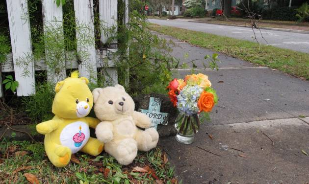 Two teddy bears, a commemorative cross and a vase of flowers sit on a street corner in Brunswick, Ga. on Saturday, March 23, 2013, near where a 13-month-old baby was fatally shot in his stroller two days earlier. Sherry West says her son, Antonio Santiago, was shot in the face by a gunman after she refused to give him money. (AP Photo/The Morning News, Russ Bynum)