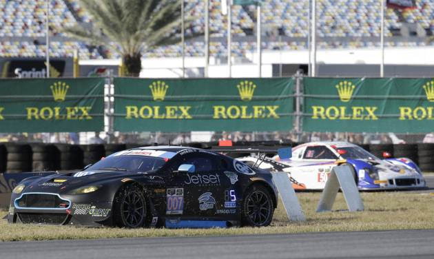 James Davison, left, of Australia, drives in the infield grass to get back on the track after a spinout in the horseshoe turn during  the IMSA Series Rolex 24 hour auto race at Daytona International Speedway in Daytona Beach, Fla., Saturday, Jan. 25, 2014.(AP Photo/John Raoux)