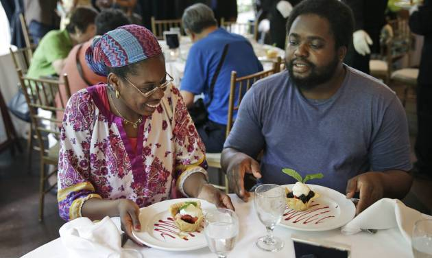 "Sharon Robinson, left, and Roy Gantt, both residents of the New York City Rescue Mission, look over their just served desserts at The Loeb Boathouse restaurant in New York, Wednesday, June 25, 2014.  Recycling magnate Chen Guangbiao,  known for his sometimes eccentric gestures served up a fancy lunch Wednesday to hundreds of homeless New Yorkers at a Central Park restaurant and serenaded them with ""We are the World."" (AP Photo/Seth Wenig)"