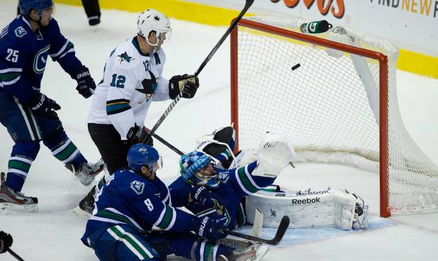 Vancouver Canucks' Mike Santorelli, left, Chris Tanev, bottom, goalie Roberto Luongo and San Jose Sharks' Patrick Marleau, 12, watch as the puck enters the net for the winning goal off the stick of Sharks' Dan Boyle, not seen, during overtime NHL hockey action in Vancouver, British Columbia, on Thursday Nov. 14, 2013. (AP Photo/The Canadian Press, Darryl Dyck)