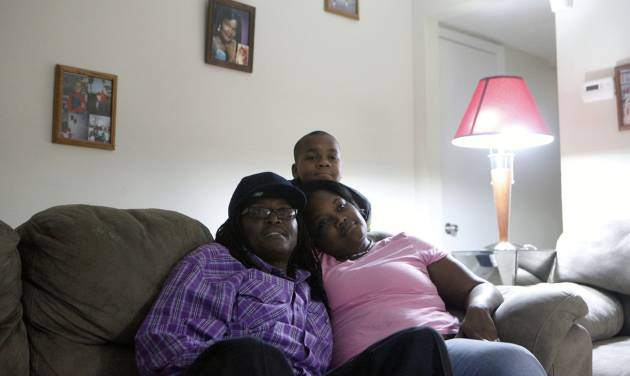 "Veteran Larry Mainor, 48, left, who was homeless for nearly 30 years, watches a football game on T.V.  with his fiancé Naketta Virella and her 11-year-old son TaDarios Virella in Mainor's home, Saturday, Aug. 17, 2013, in Decatur, Ga. Atlanta's ""Unsheltered No More"" initiative is currently working to place homeless veterans and the chronically homeless, like Mainor, into permanent housing. The city is on-track to end chronic and veteran homelessness by 2015. (AP Photo/Jaime Henry-White)"