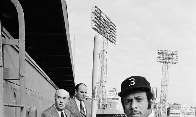 FILE- In this Jan. 18, 1973, file photo, Orlando Cepeda, right, swings a bat for photographers after the Boston Red Sox announced they had signed Cepeda as their first designated hitter at Fenway Park in Boston. General manager Dick OConnell, left, and Haywood Sullivan, vice president, player personnel, watch. The DH is 40 years old this season, and Cepeda is headed to Boston next month to help celebrate the anniversary. He will be recognized at Fenway Park on May 8, 2013. (AP Photo/ File)