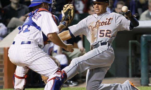 Chicago Cubs catcher Steve Clevenger, left, takes a throw from left fielder Alfonso Soriano before tagging out Detroit Tigers' Quintin Berry during the eighth inning of an interleague baseball game Wednesday, June 13, 2012, in Chicago. Berry tried to score from second on a single by Brennan Boesch that scored Gerald Laird. (AP Photo/Charles Rex Arbogast)
