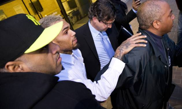Singer Chris Brown is surrounded by bodyguards as he departs the H. Carl Moultriel courthouse Monday, Oct. 28, 2013, with one of his attorney's, Danny Onorato, center,, in Washington. A charge against the Grammy Award-winning R&B singer has been reduced to a misdemeanor and he was ordered released after his arrest Sunday following an altercation outside a Washington hotel. (AP Photo/ Evan Vucci)