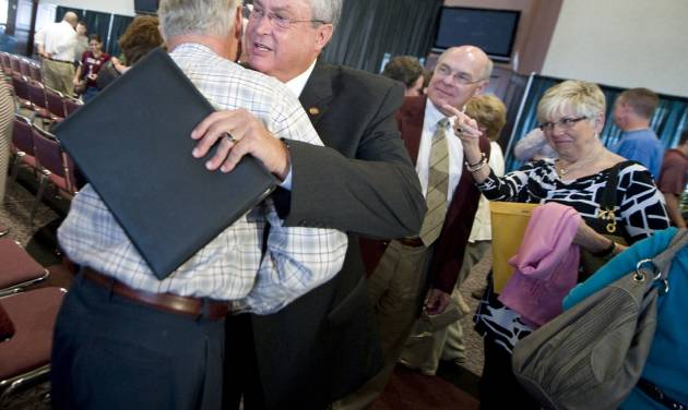 Bill Byrne, second from left, gets a hug after announcing his retirement as athletic director at Texas A&M during a news conference in College Station, Texas, Tuesday, May 8, 2012. A&M won 45 Big 12 championships in 13 different sports under the 66-year-old Byrne. (AP Photo/College Station Eagle, Stuart Villanueva)