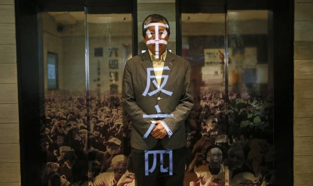 """In this May 28, 2014 photo, Lee Cheuk Yan, head of the pro-democracy group that operates the June 4th Museum, poses after an interview at the museum in Hong Kong. The 75 square meters (800 square feet) June 4th Museum is the world's only museum chronicling the brutal crackdown on the 1989 Tiananmen protests. The Chinese words project on Lee are """" Exonerate the June 4."""" (AP Photo/Vincent Yu)"""