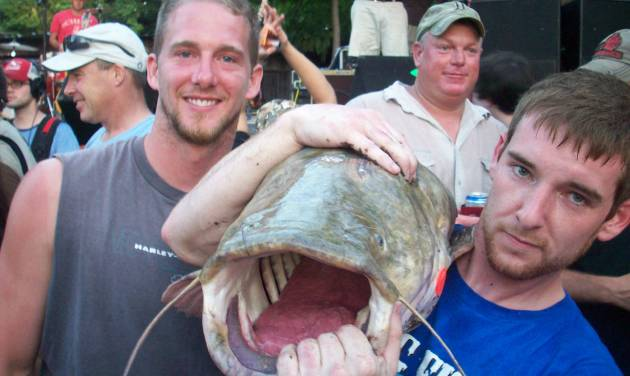 "Jesse Hansen of Plainview, Minn., holds a flathead catfish caught by another noodler at last year's Okie Noodling Tournament in Pauls Valley. Hansen hopes to become a ""real Okie noodler"" this year by catching his own fish with his bare hands. Photo provided"