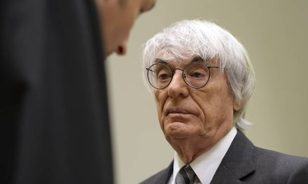 """Formula One boss Bernie Ecclestone, right, waits prior to the fourth day of his trial at the courthouse in Munich, southern Germany, Tuesday, May 13, 2014. Ecclestone is charged with bribery and incitement to breach of trust """"in an especially grave case"""" over a US dollar 44 million payment to a German banker, that prosecutors allege was meant to facilitate the sale of the Formula One Group to a buyer of Ecclestone's liking. (AP Photo/Christof Stache, Pool)"""
