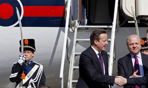 British Prime Minister David Cameron, center, arrives at Schiphol airport in Amsterdam on Monday March 24, 2014 ahead of the March 24-25 Nuclear Security Summit (NSS) in The Hague. (AP Photo/Martijn Beekman, POOL)