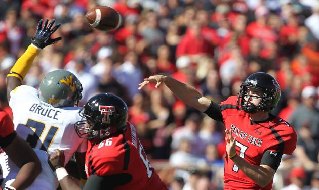 Texas Tech's Seth Doege throws over West Virginia's Isaiah Bruce while getting a block from Deveric Gallington (66) during their NCAA college football game in Lubbock, Texas, Saturday, Oct. 13, 2012. (AP Photo/Lubbock Avalanche-Journal, Stephen Spillman)