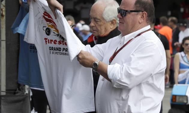 Car owners Roger Penske, left, and Chip Ganassi sign autographs for fans before practice for the IndyCar Firestone Grand Prix of St. Petersburg auto race Friday, March 28, 2014, in St. Petersburg, Fla. The race takes place on Sunday. (AP Photo/Chris O'Meara)