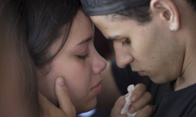 **CORRECTS GENDER OF MOURNER ON RIGHT**A woman weeps as she is comforted by a man during the funeral of Gustavo Goncalves, the most recent victim of the Kiss nightclub fatal fire raising the death toll to 235, in Santa Maria, Brazil, Wednesday, Jan. 30, 2013. A fast-moving fire roared through the crowded, windowless nightclub in this southern Brazilian city early Sunday.  The first funeral services were held Monday for the victims. Most of the dead were college students 18 to 21 years old, but they also included some minors. (AP Photo/Felipe Dana)