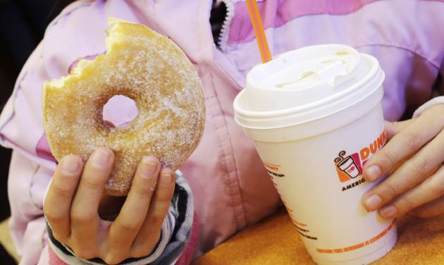 A girl has a doughnut and a beverage, served in a foam cup, at a Dunkin' Donuts in New York Thursday, Feb. 14, 2013. New York Mayor Michael Bloomberg, who has taken on smoking, sugary drinks and salt, talked about banning food packaging made from polystyrene foam from stores and restaurants in his annual State of the City address on Thursday. (AP Photo/Mark Lennihan)