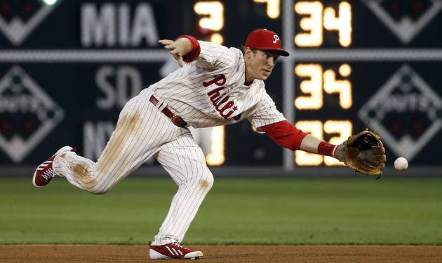 Philadelphia Phillies second baseman Chase Utley chases down a ground ball hit by Chicago Cubs' John Baker during the fourth inning of a baseball game, Friday, June 13, 2014, in Philadelphia. Baker was out on the play. (AP Photo/Matt Slocum)