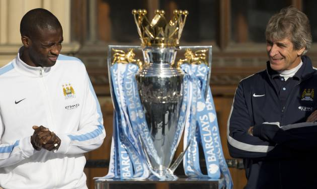 Manchester City's Yaya Toure, left, and manager Manuel Pellegrini stand by the trophy as the team celebrate in the city centre the day after they won the English Premier League title, Manchester, England, Monday May 12, 2014. (AP Photo/Jon Super)