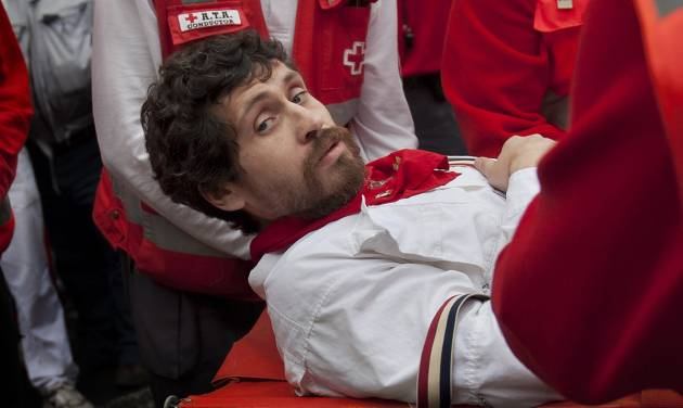 "U.S. runner Bill Hillmann, 35, from Chicago, Ill., is carried on a stretcher after being gored on his right leg by a Victoriano del Rio ranch fighting bull during the running of the bulls at the San Fermin festival in Pamplona, Spain, Wednesday, July 9, 2014. A journalist and author, Hillmann, is a veteran San Fermin runner and has written many pieces about the festival. The injury was said to be serious but his life was not in any danger. Revelers from around the world arrive in Pamplona every year to take part on some of the eight days of the running of the bulls glorified by Ernest Hemingway's 1926 novel ""The Sun Also Rises."" (AP Photo/M.J. Arranz)"