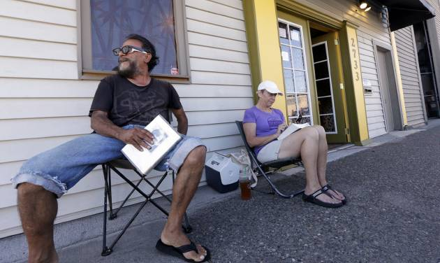 George Vargas, left, takes a seat next to first-in-line customer Deb Greene in front of the recreational marijuana store Cannabis City Monday, July 7, 2014, in Seattle. The store will be the first and only store initially in Seattle to legally sell recreational pot when sales begin Tuesday. (AP Photo/Elaine Thompson)