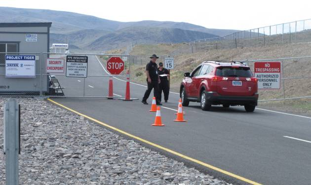 "Security guards stop a car Friday Aug. 1, 2014, at the gate to the site Tahoe Reno Industrial Center about 15 miles east of Reno, Nevada where Tesla Motors has broken ground as one of the possible places to build a $5 billion ""gigafactory'' to make lithium batteries for its electric cars. (AP Photo/Scott Sonner)"