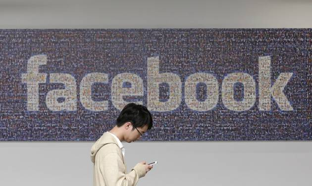 In this June 11, 2014 photo, a man walks past a Facebook sign in an office on the Facebook campus in Menlo Park, Calif. British data protection authorities said Wednesday, July 2, that it is investigating revelations that Facebook conducted a psychological experiment on its users. (AP Photo/Jeff Chiu)