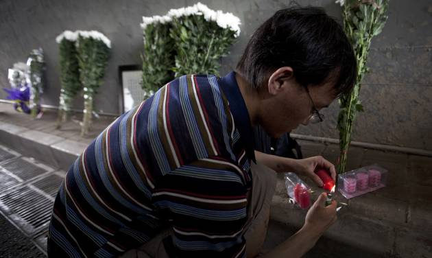 A man lights candles near the flowers placed under a railway bridge, where a motorist drowned a week ago in Beijing, China Saturday, July 28, 2012. A small group of people laid down white chrysanthemums or lit candles Saturday to pay tribute to those who died in the storm that ravaged Beijing one week ago, killing at least 77. (AP Photo/Andy Wong)