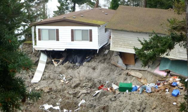 This March 27, 2013 photo provided by the Washington Dept. of Natural Resources, shows a home  that was damaged by the massive landslide that also isolated or threatened more than 30 others near Coupeville, Wash.  Geologists and engineers are assessing what might happen next after a large landside thundered down the scenic island hillside overlooking Puget Sound.    (AP Photo/Washington Dept. of Natural Resources, Stephen Slaughter)