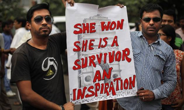 Indians hold a placard outside a court after a judge sentenced to death four men for the December rape and murder of a student on a moving New Delhi bus, in New Delhi, India, Friday, Sept. 13, 2013. The case has been closely followed across India, seen as a reflection on rampant mistreatment of women and the government's inability to deal with crime. (AP Photo/Altaf Qadri)