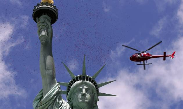 One of three helicopters showered 1-million rose petals on the Statue of Liberty during a ceremony commemorating the 70th anniversary of the D-Day invasion, on Liberty Island in New York Harbor, Friday, June 6, 2014. (AP Photo/Richard Drew)