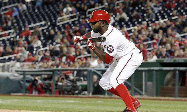 Washington Nationals' Denard Span bunts the ball, and reached second on a throwing error, during the eighth inning of a baseball game against the Miami Marlins at Nationals Park Wednesday, April 9, 2014, in Washington. The Nationals won 10-7. (AP Photo/Alex Brandon)