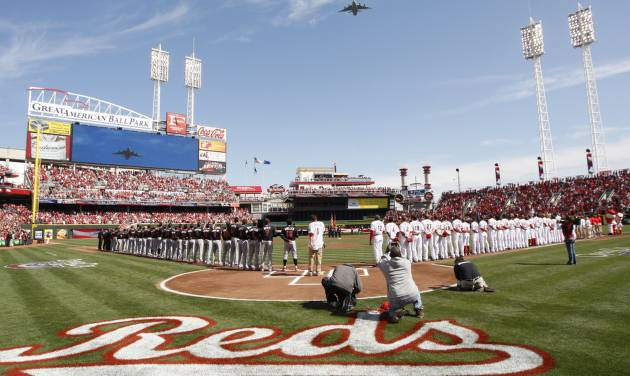 The Cincinnati Reds and the Miami Marlins stand on the field during the National Anthem prior to an Opening Day baseball game, Thursday, April 5, 2012, in Cincinnati. (AP Photo/David Kohl)