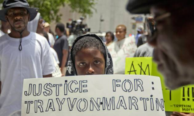 Jerald Eggleston, 10, holds a sign as he joined the more than 100 protestors organized outside the Bob Casey Federal Courthouse in Houston in reaction to the acquittal of neighborhood watch member George Zimmerman Tuesday, July 16, 2013. Protests have been held nationwide since jurors acquitted Zimmerman Saturday for the shooting death of unarmed teenager Trayvon Martin. Many of the posters carried by the protesters in Houston had a picture of Martin in his hooded sweatshirt. (AP Photo/Houston Chronicle, Johnny Hanson)