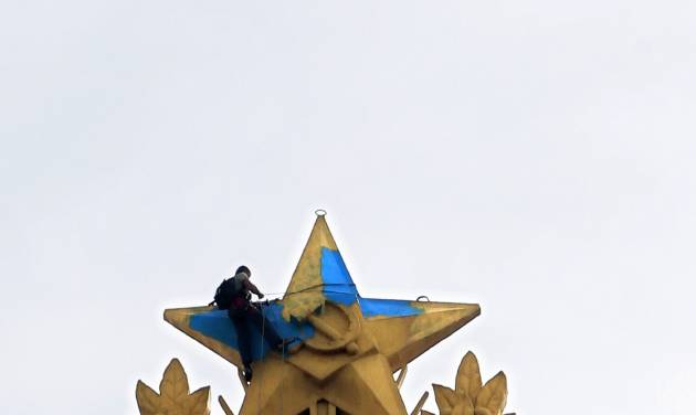 CORRECTS THAT THE MAN WAS PAINTING OVER THE STAR WHICH WAS PREVIOUSLY PAINTED IN UKRAINIAN  COLOURS BY A PROTESTER   A man paints  yellow over the blue at one of Moscow's Stalin-era skyscraper with a star on top, which was painted in colors of Ukrainian national flag in Moscow, Russia, Wednesday, Aug. 20, 2014.   (AP Photo/Ivan Sekretarev)