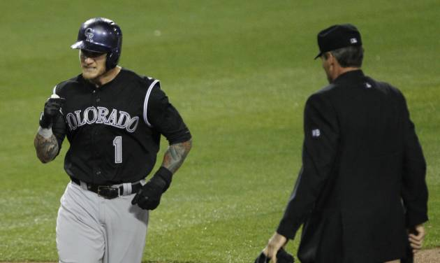 Colorado Rockies' Brandon Barnes (1) pumps his fist after scoring on a single by Rockies' Charlie Blackmon in the eleventh inning as home plate umpire Angel Hernandez, right, watches in a baseball game against the Los Angeles Dodgers on Friday, April 25, 2014, in Los Angeles. Rockies won the game 5-4 in eleven innings. (AP Photo/Alex Gallardo)
