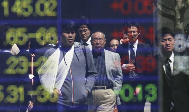 People are reflected on the electronic board of a securities firm in Tokyo, Friday, April 11, 2014. Tokyo's Nikkei 225 stock average fell more than 400 points at one point in morning trading. (AP Photo/Koji Sasahara)