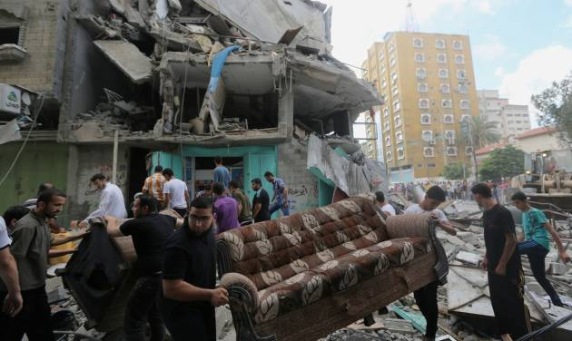 Palestinians salvage their usable belongings from the rubble of their homes in an apartment building after it was hit by an Israeli missile strike in Gaza City, Friday, July 18, 2014. Israeli troops pushed deeper into Gaza on Friday to destroy rocket launching sites and tunnels, firing volleys of tank shells and clashing with Palestinian fighters in a high-stakes ground offensive meant to weaken the enclave's Hamas rulers. (AP Photo/Hatem Moussa)