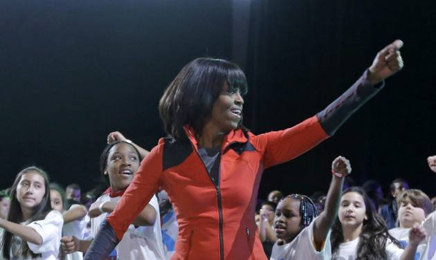 First lady Michelle Obama exercises with children from Chicago Public Schools, in her hometown of Chicago, Thursday, Feb. 28, 2013, as she makes a major announcement helping to bring back physical activity to area schools, while celebrating the third anniversary of her 'Lets Move' program.  (AP Photo/M. Spencer Green)
