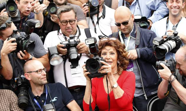 Actress Sophia Loren, front center, takes a photo as she sits with photographers during a photo call for Human Voice (Voce Umana) at the 67th international film festival, Cannes, southern France, Wednesday, May 21, 2014. (AP Photo/Alastair Grant)