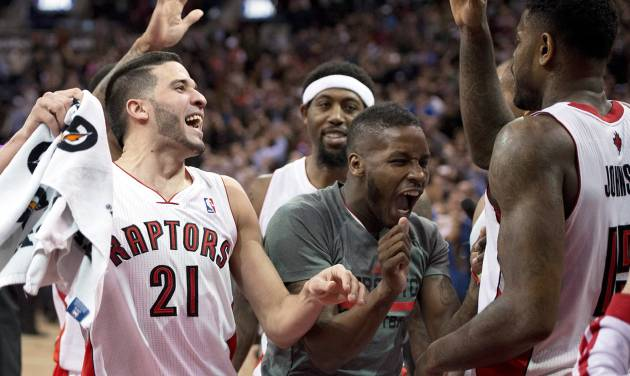 Toronto Raptors' Amir Johnson, right, who made the game winning shot, is congratulated by teammates Greivis Vasquez, left, and Dwight Buycks after defeating the Boston Celtics in NBA action in Toronto on Friday March 28, 2014. The Raptors clinched a playoff spot with the win. (AP Photo/The Canadian Press, Frank Gunn)