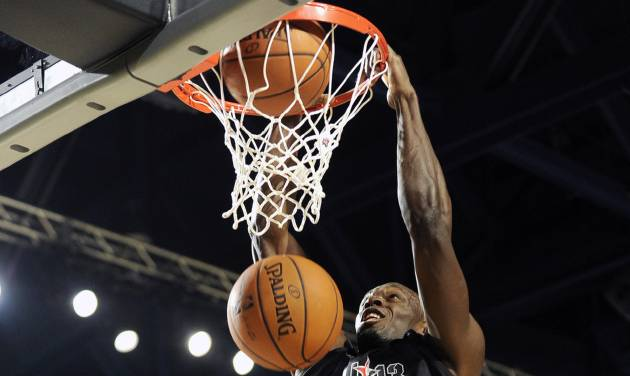 Olympic gold medalist Usain Bolt (4) dunks over comedian Kevin Hart in the first quarter of the NBA All-Stars celebrity basketball game on Friday, Feb. 15, 2013, in Houston. (AP Photo/Pat Sullivan)