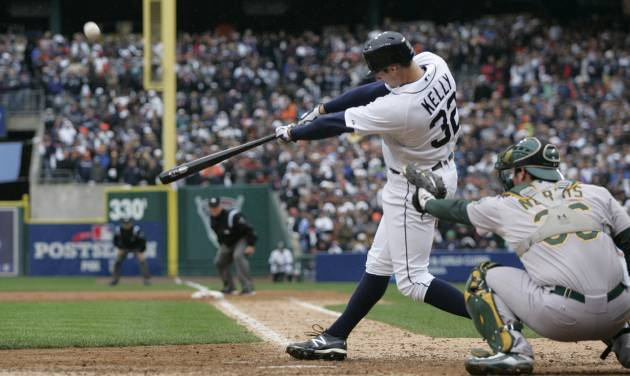 Detroit Tigers' Don Kelly hits a sacrifice fly to right to score teammate Omar Infante during the ninth inning of Game 2 of the American League division baseball series against the Oakland Athletics, Sunday, Oct. 7, 2012, in Detroit. (AP Photo/Duane Burleson)