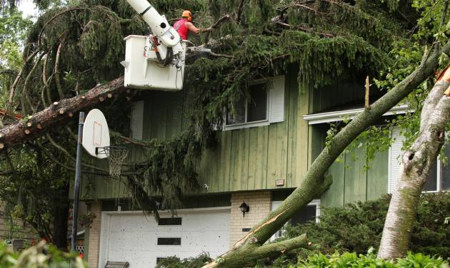 A worker removes a tree that had fallen on a home during a tornado in Madison, Wis., Wednesday, June 18, 2014. Another round of severe storms knocked down trees and power lines in and around Madison on Wednesday, a day after tornadoes caused extensive damage in the area. (AP Photo/Wisconsin State Journal, Amber Arnold)