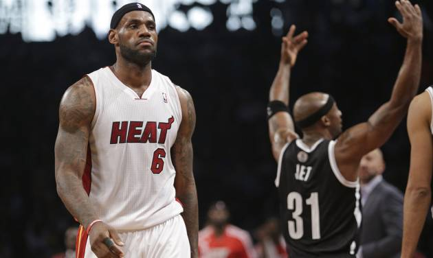 Miami Heat's LeBron James (6) walks toward the bench during a timeout in the first half of an NBA basketball game as Brooklyn Nets' Jason Terry (31) gestures to the crowd on Friday, Jan. 10, 2014, in New York. (AP Photo/Frank Franklin II)