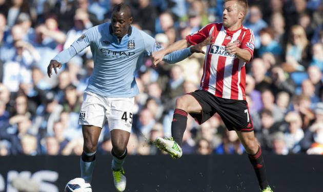 Manchester City's Mario Balotelli, left, fights for the ball against Sunderland's Sebastian Larsson during their English Premier League soccer match at The Etihad Stadium, Manchester, England, Saturday, Oct. 6, 2012. (AP Photo/Jon Super)