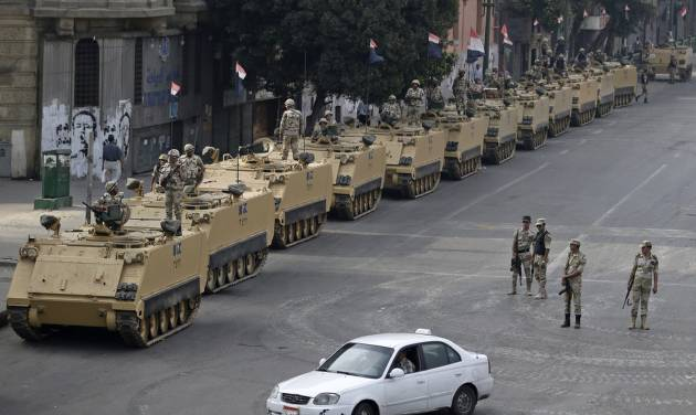 "Egyptian army soldiers take their positions on top and next to their armored vehicles while guarding an entrance to Tahrir Square, in Cairo, Friday, Aug. 16, 2013. Egypt is bracing for more violence after the Muslim Brotherhood called for nationwide marches after Friday prayers and a ""day of rage"" to denounce this week's unprecedented bloodshed in the security forces' assault on the supporters of the country's ousted Islamist president that left more than 600 dead. (AP Photo/Hassan Ammar)"