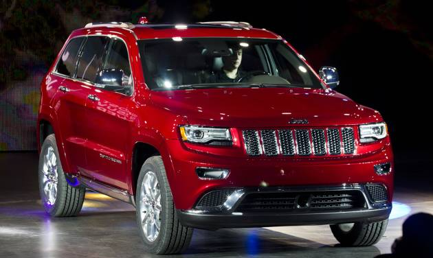 FILE - In this Jan. 14, 2013 file photo, the 2014 Jeep Grand Cherokee is introduced at the North American International Auto Show in Detroit, Mich. With the addition of an impressive diesel V-6 from Jeep's parent, Fiat of Italy, the 2014 Grand Cherokee 4X2 now boasts a federal government travel range of 615 miles on a single tank of fuel, the best ever for a Grand Cherokee. It is rated at 22 miles per gallon for city driving and 30 mpg on the highway, for an average of 25 mpg. (AP Photo/Tony Ding, File)