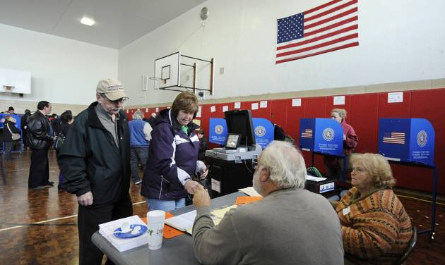 In this Nov. 6, 2012, photo, people line up to cast their votes in Lindell School in Long Beach, N.Y., one of several voting locations that was created as a result of Superstorm Sandy. Exit polls from Tuesday's election show that the voters have a plan: Consider raising taxes on the wealthy, but not everybody else. Shrink the government. Work harder on creating jobs and holding the line on prices, because they think economic worries are more important than cutting the deficit right now. (AP Photo/Kathy Kmonicek)