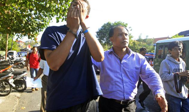 FILE - In this Wednesday, Aug. 13, 2014 file photo, an Indonesian police officer escorts American Tommy Schaefer, left, as he is brought to the police station for questioning in relation to the death of his girlfriend's mother, in Bali, Indonesia. Schaefer and his girlfriend also American Heather Mack arrested in Indonesia on suspicion of murdering the woman's mother and stuffing her body into a suitcase at a resort hotel are being held under a suicide watch, their appointed lawyer said Wednesday. (AP Photo/Firdia Lisnawati, File)
